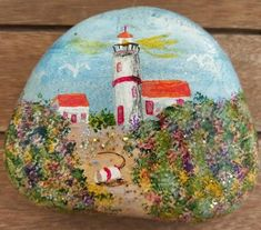 "This 4"" x 3"" flat rock has a red roofed lighthouse painted in a field of flowered sandy dunes. You can imagine the ocean is just on the other side of the hills. Yellow glistens in the sun and birds fl"