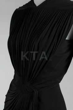 A Madame Grès black draped silk jersey evening gown, late 1930s-early 1940s, un-labelled, with pleated front bodice, cap sleeves, back slit open to the waist, draped wrap-around skirt,
