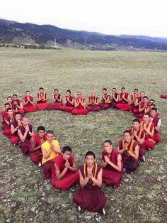 Moines tibétains formant un coeur pour la paix dans le monde.