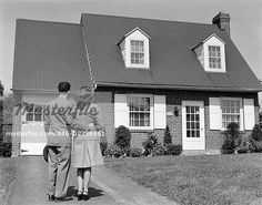 1940s COUPLE LOOKING AT SUBURBAN HOUSE