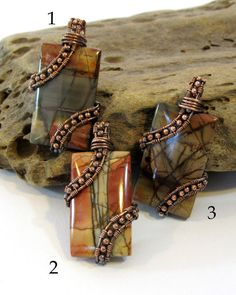 Whats not to love about Red Creek jasper? It has rich, natural earth tones and gorgeous patterning, making each piece unique. These three pendants are all wrapped in the same style, but as you can tell, each is still one-of-a-kind. The asymmetrical wire weaving on these is done with solid copper wire and beads. I oxidize these by hand to achieve the desired degree of darkness in the copper and then polish them back up to create visual dimension and show off the texture of the weaving.  Each…