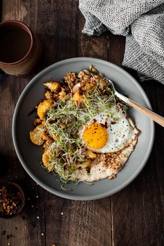 Filling Grain bowls with farro, hummus, smoky roasted cauliflower, fried eggs, and broccoli microgreens.