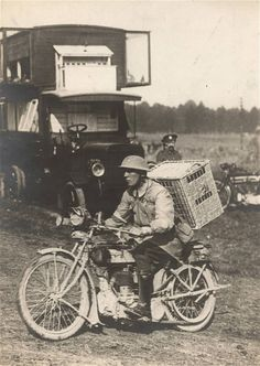 A British soldier rides a motorbike with a basket of pigeons on his back, on his way to delivering them to the frontline on the Western Front in 1916
