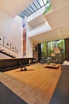 Large open sitting area features high ceilings a skylight and a large window facing an enclosed courtyard in this 4-story home located in NYC. [1062  1600]