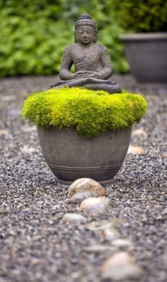 A stone Buddha meditates at the entrance to the labyrinth, setting a mood of repose reinforced by the quiet palette of moss, gravel and stones.