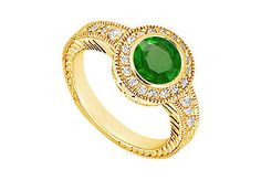 Round royal green emerald is bezel-set in the center & is surrounded by smaller round diamonds