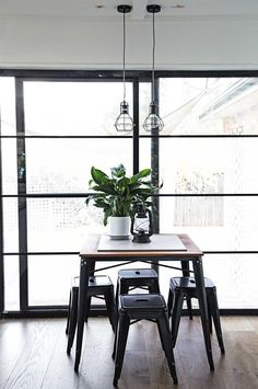 Small dining area: square wooden dining table with black legs, black Tolix stools, peace lily in white pot, black wire frame lightbulb industrial pendant lights, timber floorboards