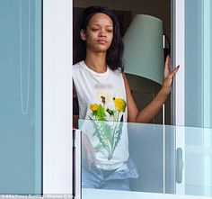 Rihanna goes make-up free as she steps out onto the balcony of her waterfront hotel in New Zealand on Sunday