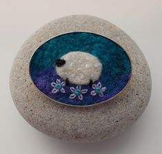 Felted Sheep Brooch Pin Handmade Felt This little felt sheep is made using wet felting and needle felting techniques. I have used hand dyed fibres for the background. The sheep is needle felted on by hand with a little bit of stitch for added detail. The felt is then mounted in a silver tone oval brooch tray measuring 3.5 x 5 cm. Comes gift wrapped in box shown. Handmade in Scotland. © Aileen Clarke