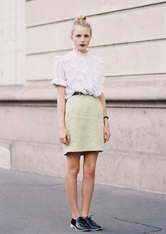 Blouse with ruffles tucked into a light green skirt and paired with oxfords