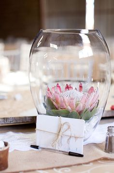 Use single flowers, like these gorgeous king protea, in large vases to add a whimsical touch to your reception tables.