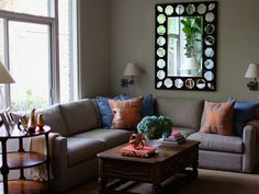 Chic gray and orange family room with greige paint color and black mirror with octagon inset mirrors.