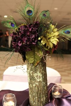 Center piece for peacock themed wedding. Made with small tree trunk. Drill hole in middle and add flowers.