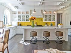 I love the bright yellow subway tile back splash in this kitchen.