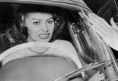 Sophiа Loren cowers in her car as a crowd of fans press around her, smashing the windscreen