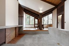 The dining room opens up to the new concrete hearth. Old plans indicate this area was originally intended to be an open courtyard, however, the original clients enclosed it with a leaky glass canopy. The architects installed a new sloped roof that quickly channels away rainfall. The fireplace is composed of brick salvaged from the original floor and the new concrete floor features increased insulation.