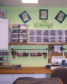 scrapbooking craft room idea... (i'm very much liking the numerous mini plastic drawers storage units arranged together atop the shelf.)