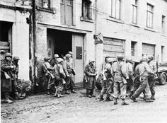 Elements of the 110th Regiment, 28th Infantry Division having reached Bastogne at the beginning of the siege, regroup outside a garage. 19 december 1944.