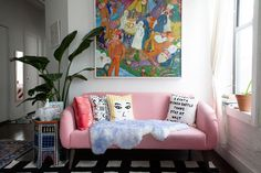 A pink sofa makes a fun statement in Aelfie Oudghiri's Brooklyn home, where the designer's pillows are on display.