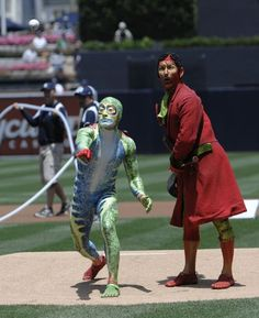 "Game #32 5/9/12: Cirque du Soleil ""Totem"" character The Green Frog throws out the first pitch as Tractor, right, looks on before a baseball game between the Colorado Rockies and the San Diego Padres at Petco Park on May 9, 2012 in San Diego, California. (Photo by Denis Poroy/Getty Images)"