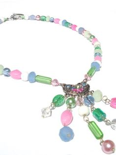 This necklace is made with  glass beads in the colors pink, blue, green and white. The necklace is completed with a silver-colored pendant.