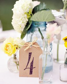 Tag-shaped cards sported rubber-stamped table numbers. They rested upon against mix-and-match vessels holding assorted flowers.