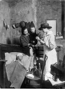 Pohled do bytu, kde ošetřovatelka pečuje o nemocné dítě. 1905