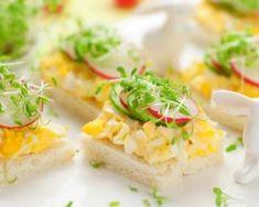 Oeufs brouillés sur canapés et petits légumes