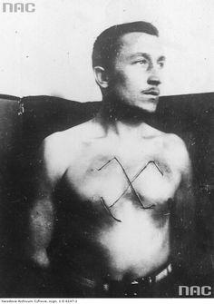 Mężczyzna z wyciętą na piersi swastyką- fotografia sytuacyjna.