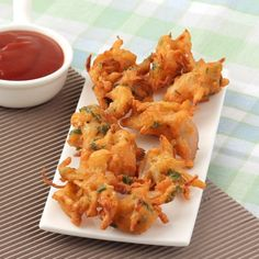 Indian style Onion Pakoda - Deep fried onion fritters are served with tomato ketchup and tea as evening snack.