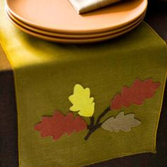 Leaf Linen Fall Table Runner  Drape this fall table runner on your dining room table. Apply iron-on backing to the back side of pretty fall-color linen. Trace garden leaves and hand-draw stem shapes onto the iron-on-backing side of the linen. Cut out the shapes, arrange them on a plain store-bought table runner, and then press them in place or secure them with tacky glue.