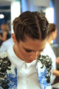 duas tranças embutidas feitas ao longo de todo o cabelo. A risca é bem definida no meio da cabeça e as duas tranças foram finalizadas em um coque baixo.