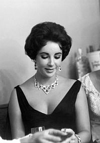 Elizabeth Taylor wearing her Cartier Ruby and Diamond Necklace, Bracelet and Earrings - a gift from husband Mike Todd while vacationing in Cap-Ferrat, France in 1957.