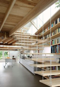 modern floating stairs + bookshelf in a Dutch barn conversion