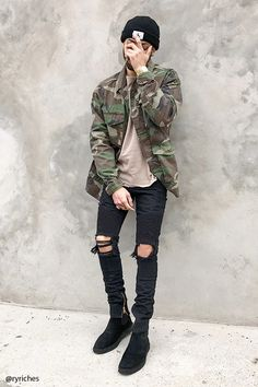 A textured woven army jacket featuring a camouflage print, basic collar, button placket, dual buttoned chest flap pockets, front flap pockets, and long button cuff sleeves.