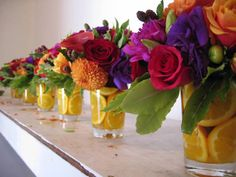 Multicoloured Floral Centrepieces in Glasses with Orange Slices