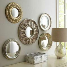 miroir de sorciere 5 de forme ronde sur un mur gris au dessus d'un meuble d'entrée blanc