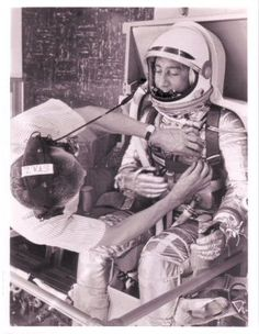 July 1961 Reclining in a contour couch in Hangar S at Cape Canaveral, Mercury Astronaut Virgil I. Grissom relaxes while adjustments are made on his full-pressure suit by Joe W Schmitt, Space Task Group Suit Specialist. NASA NO.