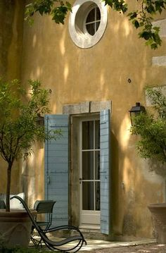 Love ochre as an exterior color. The blue shutters are so subtle against it.
