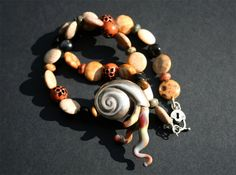 glass and metal ammonite necklace by krixbeeble on Etsy.