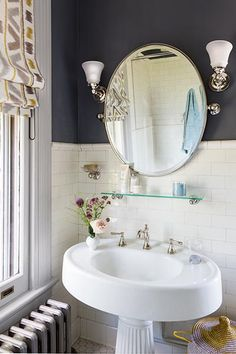 An antique fluted-pedestal sink with a Delta nickel faucet offers enough deck space for a couple of essentials; the glass shelf above adds a resting spot for other oft-used necessities. Frosted-glass sconces and a pivoting mirror complete the period look
