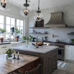 Zinc hood and oak shelves in this kitchen by Kelly Nutt Design
