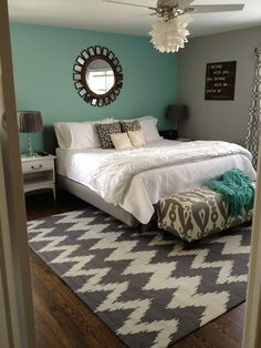 Bedroom with gray upholstered platform bed  headboard, white bedside tables a graphic print rug and a teal wall