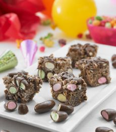 Chocolate CLINKERS Crackle Slice - A crunchy chocolate favourite with a colourful twist of CLINKERS lollies.