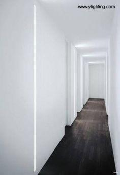 Artefactos de iluminación interior vertical embutidos en las paredes de pasillos. Diseñado por David Chipperfield