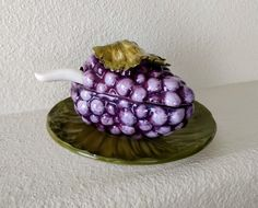 Vintage serving bowl with lid, plate, and spoon, made in Italy ca. 1950s. 4 pieces.  Grape cluster majolica in purple and olive green, with a white spoon. Stamped on bottom.  Lidded dish: 6 long, 3 3/4 wide, 3 3/4 tall.  Plate: 6 3/4 diameter, 1 tall.  Spoon: 5 long, 1 3/4 wide, 3/4 deep.   Very good vintage condition. No cracks, stains, or discoloration. There are a few tiny chips consistent with age and use: 3 on the plate edges, two on the bowls stem, two on the lid, one on the edge of…
