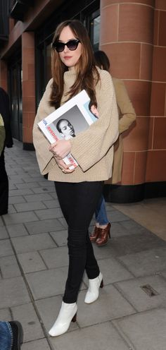 Dakota Johnson wears white patent ankle boots, a cozy knitted tunic, black jeans, and sunglasses