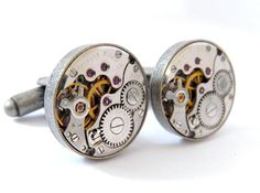 A Unique Pair of Steampunk Cufflinks  Antique Silver    These smart looking cufflinks feature two vintage mechanical watch movements.  Original red jewel bearings can be seen on their surfaces in amongst the beautifully  contrasting gold and silver colour gears and mechanics of the watches