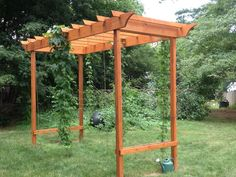Posts in ground are 4x4's stick up about 11 feet with 2 feet in the ground. Side boards are 2x10's,run 12 feet from post to post. Bracing at the top is made from 2x10's, bottom bracing: 2x4s. Roof made of 2x3's No concrete to set the posts,just gravel and rock. Climbing wires are choir rope mounted to the ground with simple garden stakes,secured at top by an S-hook attached to an eyebolt so that I can easily take the vines down for harvest.