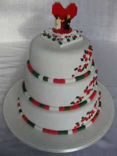 3 tier stacked white wedding cake.  Lego theme design in red, green and white.